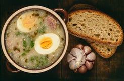 Traditionell polsk vit borscht - zurek, sur soppa med vita korvar och ägg arkivbild