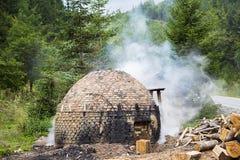 Traditionell produktion av kol i skogen arkivbild