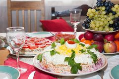 Traditionell rysk salladsill under ett pälslag på en stor vit maträtt som dekoreras med gräsplaner och ägg med den röda kaviaren arkivbild