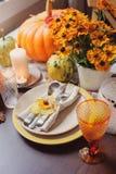 Traditionell säsongsbetonad tabell för höst som hemma ställer in med pumpor, stearinljus och blommor Arkivbilder