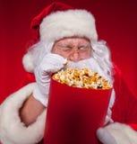 Traditionell Santa Claus för närbildstående som hållande ögonen på TV äter popcorn Jul Röd bakgrund sinnesrörelser skräck Royaltyfri Bild