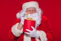 Traditionell Santa Claus hållande ögonen på TV som äter popcorn Jul Röd bakgrund sinnesrörelseskräcköverraskning Fotografering för Bildbyråer