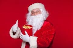 Traditionell Santa Claus hållande ögonen på TV som äter popcorn Jul Röd bakgrund sinnesrörelseskräcköverraskning Arkivfoto