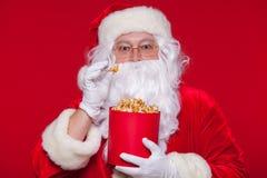 Traditionell Santa Claus hållande ögonen på TV som äter popcorn Jul Röd bakgrund sinnesrörelseskräcköverraskning Arkivfoton