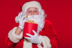 Traditionell Santa Claus hållande ögonen på TV som äter popcorn Jul Röd bakgrund sinnesrörelseskräcköverraskning Royaltyfria Bilder