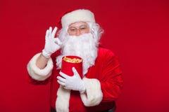 Traditionell Santa Claus hållande ögonen på TV som äter popcorn Jul Röd bakgrund sinnesrörelseskräcköverraskning Royaltyfri Foto