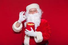 Traditionell Santa Claus hållande ögonen på TV som äter popcorn Jul Röd bakgrund sinnesrörelseskräcköverraskning Royaltyfri Bild