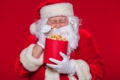 Traditionell Santa Claus hållande ögonen på TV som äter popcorn Jul Röd bakgrund sinnesrörelseskräcköverraskning Arkivbilder