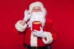 Traditionell Santa Claus hållande ögonen på TV som äter popcorn Jul Röd bakgrund sinnesrörelseskräcköverraskning Arkivbild