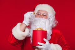 Traditionell Santa Claus hållande ögonen på TV som äter popcorn Jul Röd bakgrund sinnesrörelseskräcköverraskning Royaltyfri Fotografi