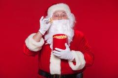 Traditionell Santa Claus hållande ögonen på TV som äter popcorn Jul Röd bakgrund sinnesrörelseskräcköverraskning Royaltyfria Foton