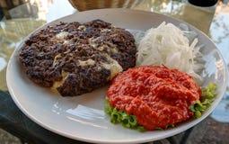 Traditionell serb och balkan maträtt Pljeskavica med sås, Maribor, Slovenien royaltyfri fotografi