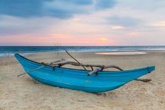 Traditionell srilankesisk fiskebåt på den sandiga stranden på solnedgången. Arkivbild