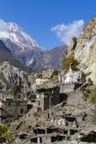 Traditionell stenbyggandeby av Manang Berg i bakgrunden Annapurna område, Himalaya, Nepal arkivfoton