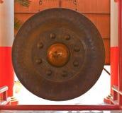 Traditionell thailändsk gong framme av kyrklig insida tempelet Arkivfoto