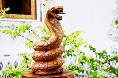 Traditionell thailändsk stilträskulptur som djur tränolla för orm en Arkivbilder