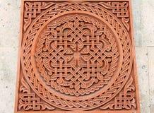 Traditionell tufasten som snider prydnaden på en vägg av den armeniska ortodoxa kyrkan arkivbild