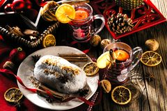 Traditionell tysk jultårta - Cranberry Stollen, julgran, prydnadar och stearinljus arkivbild