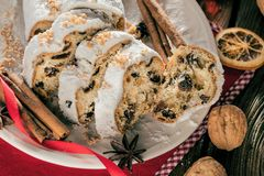 Traditionell tysk jultårta - Cranberry Stollen, julgran, prydnadar och stearinljus arkivfoton