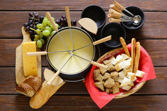 Traditionell uppsättning av redskap för fondue, med bröd, ost royaltyfri foto