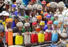 Traditionella afrikanska trähandgjorda dockor med snäckskal och färgrik pärlgarnering på det lokala hantverket marknadsför, Cape  Fotografering för Bildbyråer