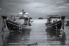 Traditionella asiatiska fartyg för asiatiskt livsstillandskap i det lugna havet under mörk lynnig solnedgång royaltyfria bilder
