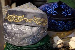 Traditionella asiatiska huvudbonader fr?n en m?ngf?rgad filt med en broderad kul?r tr?d av den nationella prydnaden royaltyfri bild