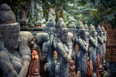 Traditionella asiatiska skulpturer av buddismgudar i tappningstil i tropisk trädgårds- illustrerande asiatisk kultur och asiatisk Arkivfoto