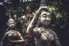 Traditionella asiatiska stenskulpturer av dansfolk i traditionell kläder i trädgård på den tropiska ön i Thailand Arkivfoton