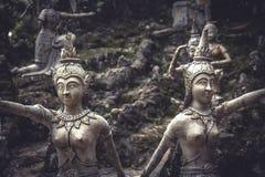 Traditionella asiatiska stenskulpturer av kvinnor i traditionella dräkter i trädgård på den tropiska ön i Thailand Royaltyfria Foton
