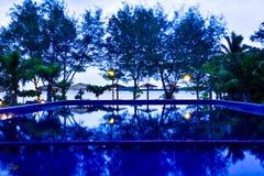 Traditionella avkopplingkojor på stranden med den blåa simbassängen i den nya morgonsoluppgången royaltyfri fotografi