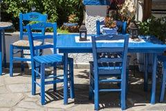 Traditionella blåa grekstolar i en trädgård Fotografering för Bildbyråer