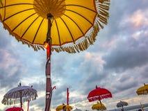 Traditionella ceremoniella paraplyer och flaggor på stranden på ceremoni Royaltyfri Bild