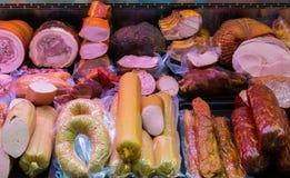 Traditionella europeiska korvar och kött i ett shoppafönster Arkivfoto