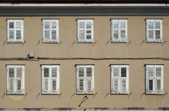 Traditionella europeiska träslutare på en brun fasad av en gammal bostads- byggnad Royaltyfri Foto