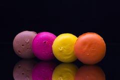 Traditionella franska färgrika macarons på det svarta glass skrivbordet Royaltyfria Foton
