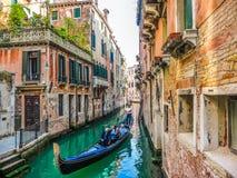Traditionella gondoler på den smala kanalen mellan färgrika hus, Venedig, Italien Arkivbild