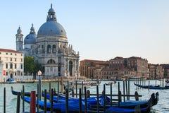 Traditionella gondoler på kanalen som är stor med basilikadi Santa Maria della Salute Fotografering för Bildbyråer