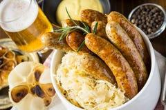 Traditionella grillade korvar med kålsallad, senap och öl Fotografering för Bildbyråer