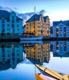 Traditionella högväxta norska hus reflekterade i en lugna kanal i Alesund, den mest härliga staden i den västra kusten av Norge royaltyfri foto