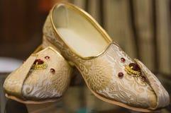Traditionella hinduiska skor eller jutis som är slitna vid en brudgum Arkivbild
