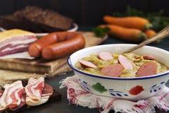 Traditionella holländska ärtsoppa och ingredienser på en lantlig tabell Arkivbild