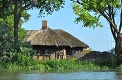 Traditionella hus med det halmtäckte taket i Donaudeltan Royaltyfri Bild