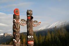 Traditionella kanadensiska infödda totempålar på Sunwapta Falls Royaltyfria Bilder