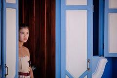 Traditionella kvinnor för thailändsk stil som står mot en blå dörr Royaltyfri Fotografi