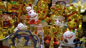 Traditionella Maneki Neko lyckliga kattstatyetter på skärm på en marknad i Saigon, Vietnam stock video