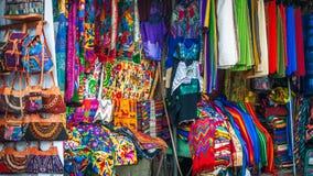 Traditionella Mayan kläder och filtar på marknaden i Panajachel Arkivfoton
