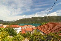Traditionella medelhavs- hus med röda belade med tegel tak och Adriatiskt havet, Dalmatia, Kroatien Arkivfoto
