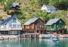 Traditionella norska hus, blått vatten och gröna färger av naturen royaltyfri bild