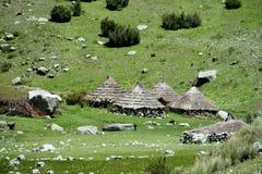 Traditionella quechua byhus med det koniska sugrörtaket Royaltyfri Foto